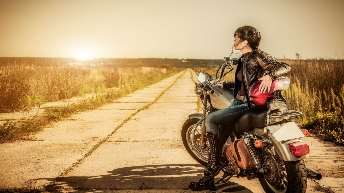 Девушка на мотоцикле на дороге фото