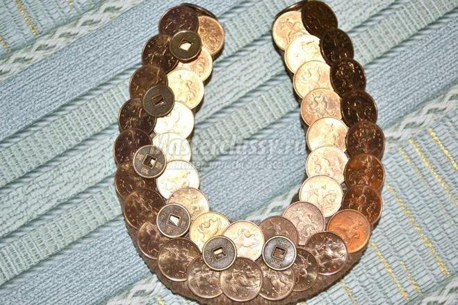 Считается что подделки из монет является символом богатства. Ну или привлечения богатства. А подкова это привлекает счастье в до