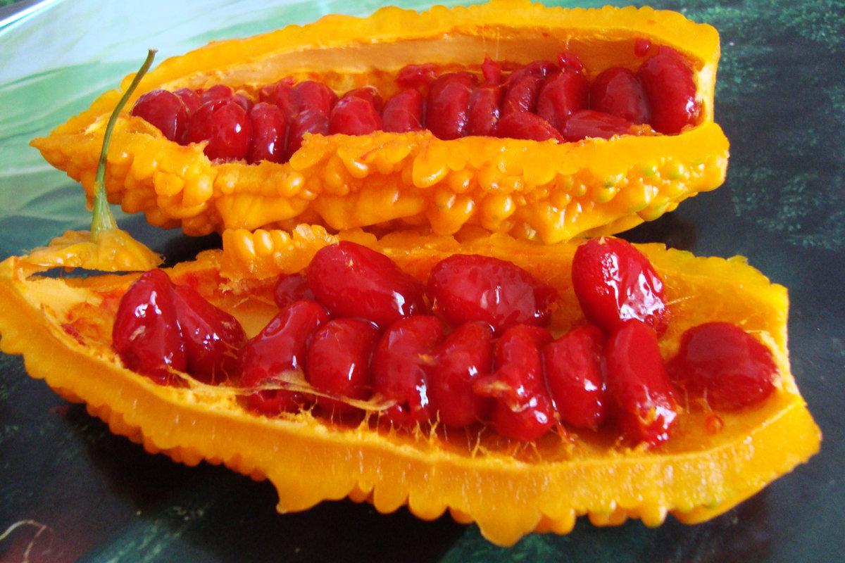 Оранжевый фрукт с красными ягодами внутри фото