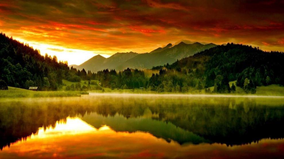 Озеро на закате отражающее осенний пейзаж.