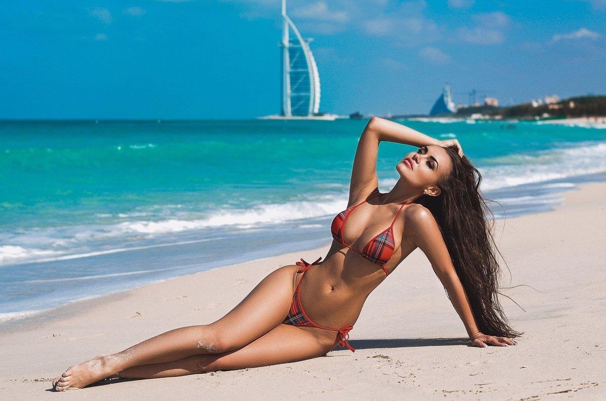длинноволосая красивая девушка в купальнике в клетку сидит на пляже