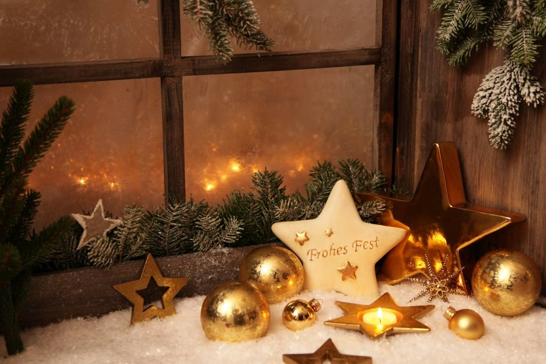 звездочки, еловые ветки и шарики на фоне окна