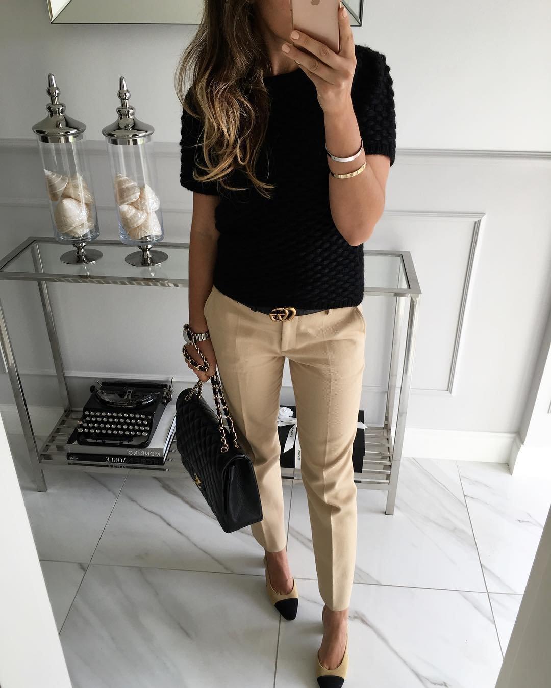 Укороченные брюки, черный верх и черная сумочка.