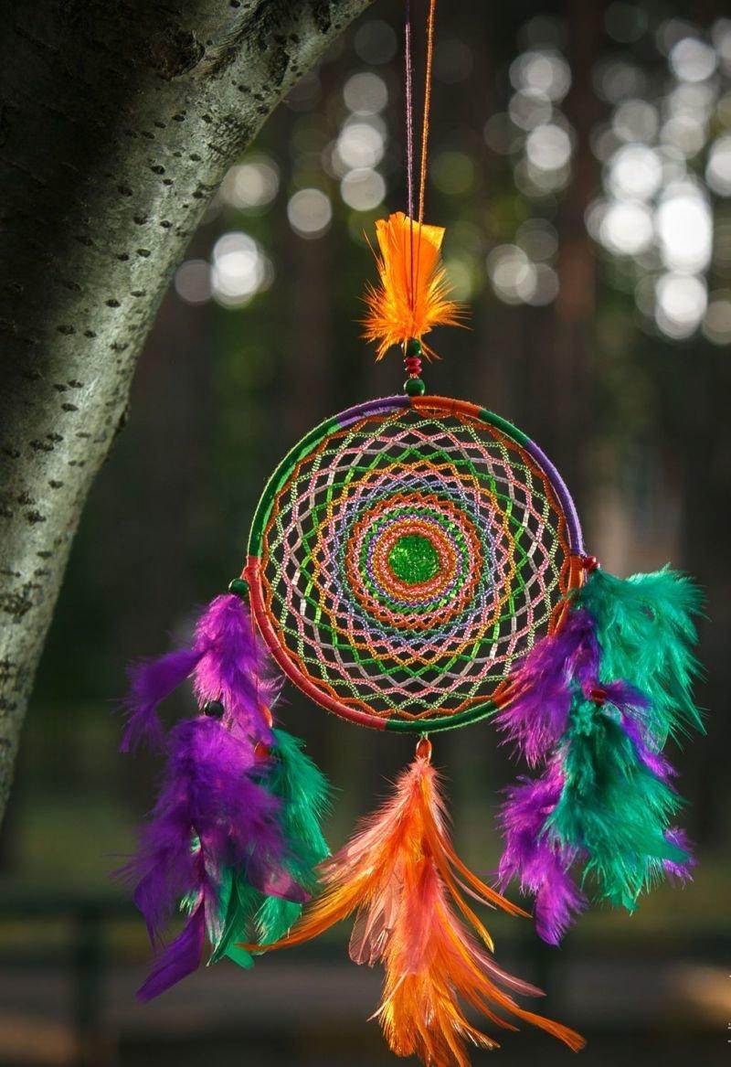 Оно выглядит как круг обруч со скрещенными в центре линиями и подвесками-перьями внизу.