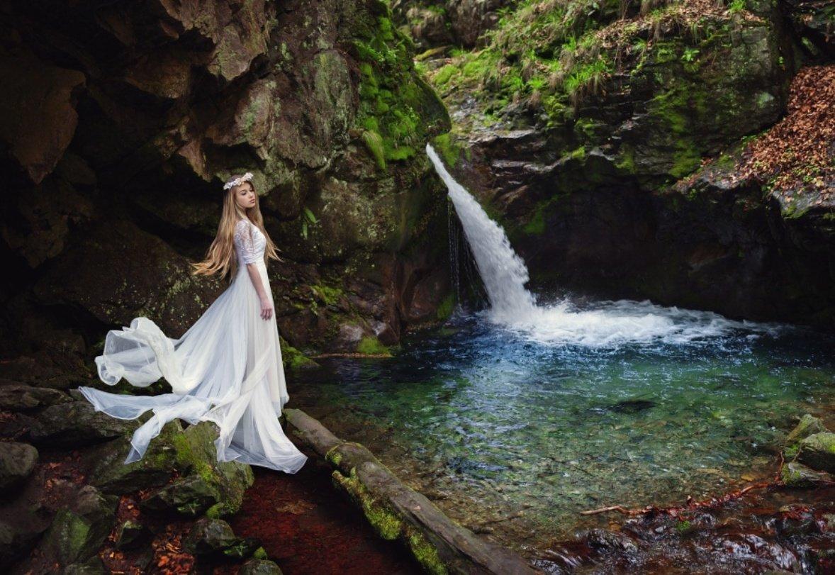Девушка под водопадом камни