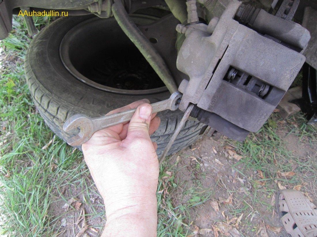 Отвернем нижний болт крепления скобы от направляющих пальцев суппорта