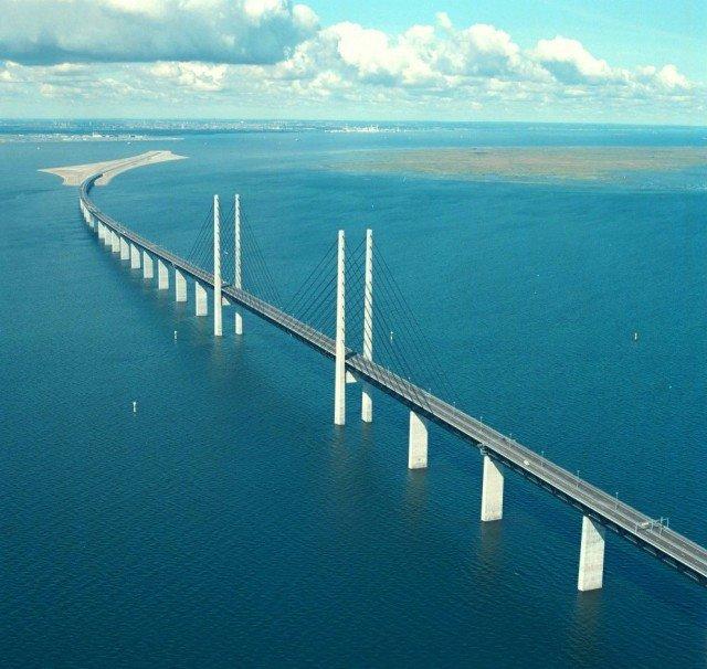 Эресунн мост (Oresun, Öresundsbron), соединяющие столицу Дании Копенгаген и шведский город Мальмё, необычен своими размерами и функциональностью. Во-первых это мост + подводный тоннель, через который проходит автомагистраль и 2-х колейная железная дорога. Во-вторых, новый мост совершенно не мешает судоходству. Мост Эресунн – самая длинная совмещенная дорога и железнодорожный мост в Европе. До его строительства жители Дании и Швеции ездили из страны в страну исключительно на паромах. Дополнительный бонус от строительства этого необычного моста отметили европейские экологи, – фундамент опор очень понравился местным моллюскам, популяция которых в последние годы в Эресуннском проливе сокращалась.