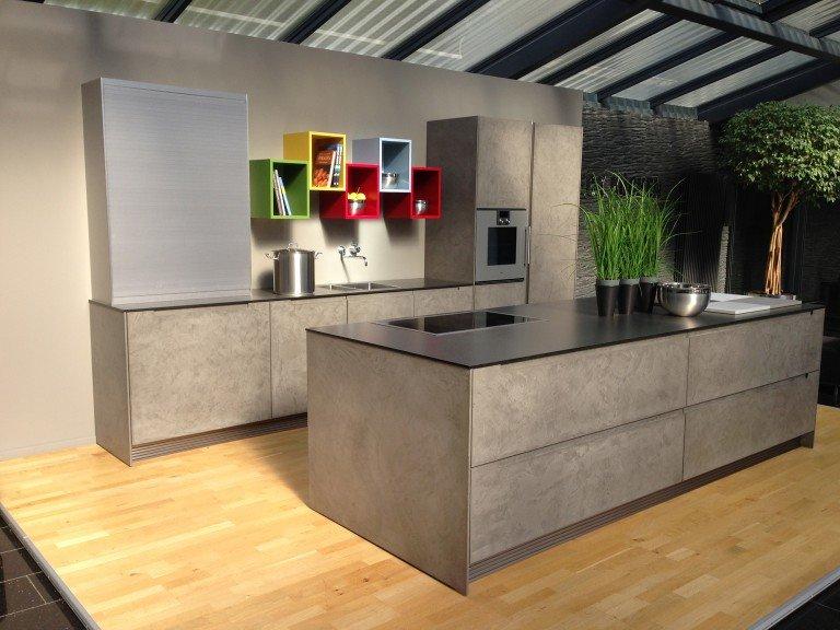 светло-серого цвета лаконичная кухня с яркими разноцветными полками и большим островом с варочной панелью