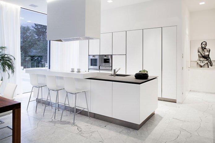 белоснежная кухня с открытым пространством и большим прямоугольной формы островом с черной столешницей и мойкой