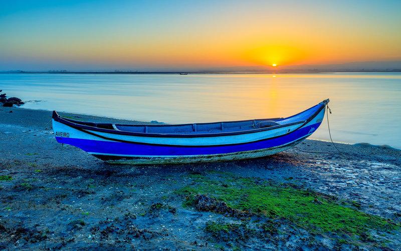 Лодка на берегу реки на закате солнца