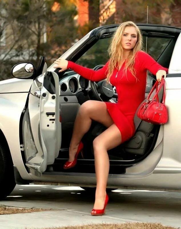 девушка в короткой юбке что-то ищет в салоне автомобиля