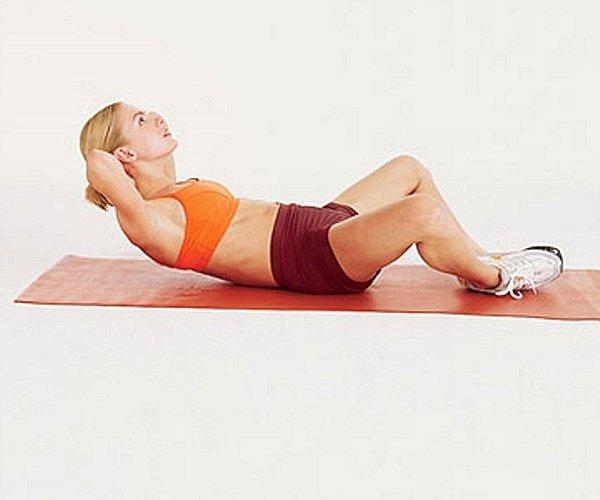 Ляг на спину, согни ноги в коленях и разведи ноги в стороны, держи стопы вместе, а руки за головой. Не сгибая спину, немного приподними корпус и задержись в таком положении на пару секунд. Опустись в исходное положение. Повтори упражнение 10 раз.
