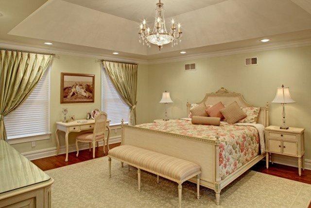 спальня со стенами и текстилем бледного мятного цвета и классической мебелью