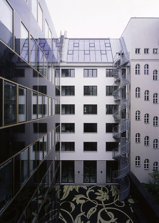 Торгово-офисный комплекс возник на месте бывшего британского посольства в Восточном Берлине. Здание 1971 года постройки является частью сложившегося ансамбля бульвара Унтер-ден-Линден, расположенного в историческом квартале Берлина Доротеенштадт, поэтому к его реконструкции архитекторы подошли с чрезвычайной ответственностью.    Конструктивный каркас сооружения был полностью сохранен, равно как и деликатно отреставрированный главный фасад, обращенный к Унтер-ден-Линден. А вот со стороны внутреннего двора бывшее посольство приобрело новый корпус, который и по своему силуэту, и по отделке фасадов старается дистанцироваться от предшественника. Он отделан черным полированным камнем и золотистым металлом, из которого выполнены элегантные горизонтальные и вертикальные  пояса  и обрамления окон.  Перемычка  между зданиями полностью остеклена, визуально обозначая четкую границу старым и новым.