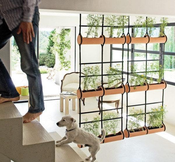 Зонирование пространства с помощью подвесных кашпо с цветами.