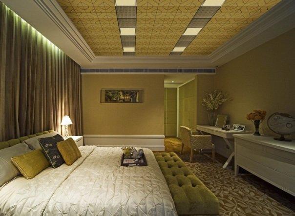 темно-оливковый цвет стен и кровать оливкового цвета в спальне с красиво оформленным потолком
