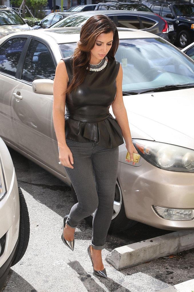 Для прогулки Ким выбрала джинсы скини, и модный в этом сезоне топ с баской, дополнив образ туфлями Jimmy Choo