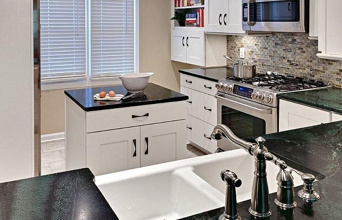 белая кухня с фурнитурой и столешницей темного цвета и маленьким прямоугольным островом со шкафом и ящиком