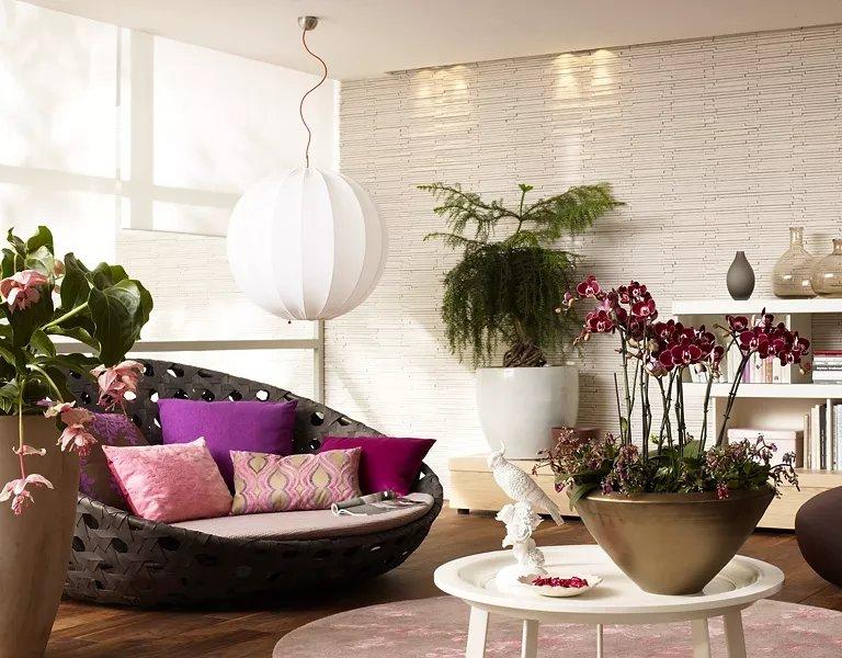 Растения в гостиной с плетеным округлым диваном