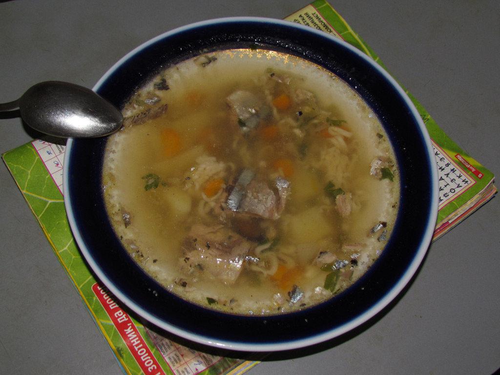 Переложить рыбу в двухлитровую кастрюлю, залить водой, добавить разрезанную на 4 части морковку, луковицу и немного зелени.
