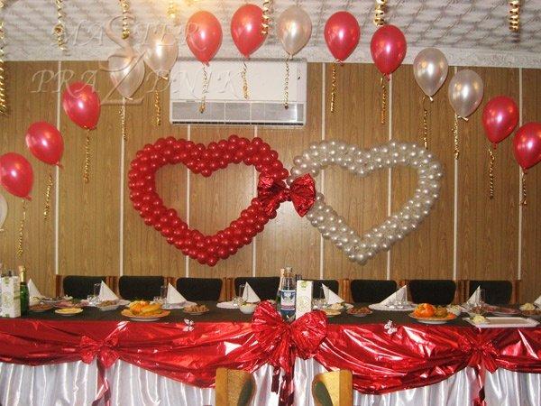 Два сердца из воздушных шаров, связанные бантом, драпировка стола полисилком.