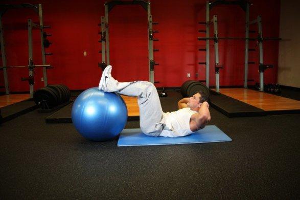 1. Постелите на пол гимнастический коврик и лягте на него спиной. Положите ноги на фитбол и согните колени под углом 90 градусов.  2. Ступни находятся на расстоянии 8-10 см, носки сведены. Руки заведите за голову, а локти направьте внутрь. Прижмите поясницу к полу, чтобы изолировать работу мышц брюшного пресса.  3. На выдохе осуществите скручивание, поднимая плечи от пола, упираясь поясницей в пол так сильно, насколько возможно. Плечи отрываются от пола не более, чем на 10 см, а поясница все время остается прижатой к полу. В конце движения максимально напрягите мышцы пресса и сделайте небольшую паузу.   4. На вдохе постепенно вернитесь в исходное положение.  5. Выполните нужное количество повторений.