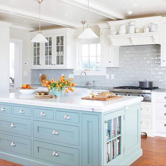 кухня в белом цвете с большим островом бледно-голубого цвета с белой столешницей
