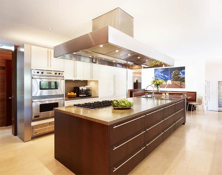 просторная кухня с большим прямоугольной формы островом и большой вытяжкой над ним