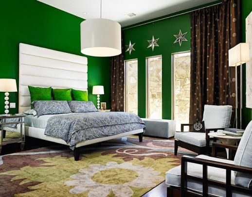 стены яркого красивого зеленого цвета и декоративные подушки на кровати в тон стенам