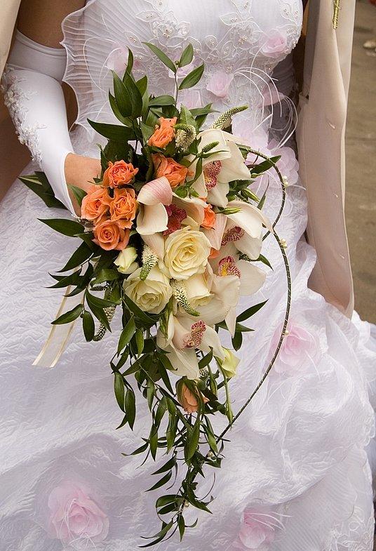 свадебный букет каскадный  из роз и орхидей и зелеными листочками