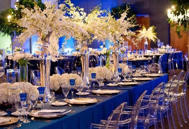 Красивое сочетание белых цветов в высоких в вазах с синей яркой скатертью