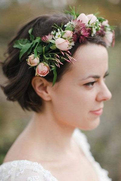 Прическа для невесты с цветочным венком в волосах.