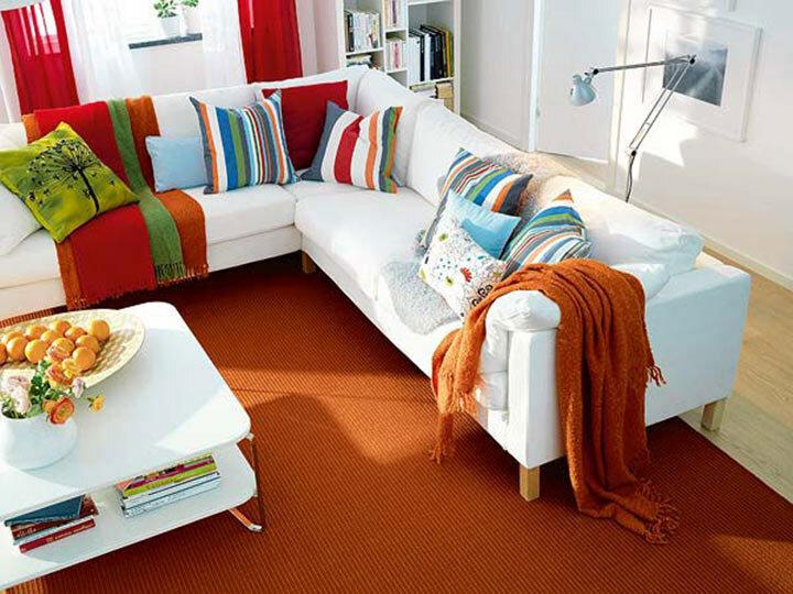Современный дизайн гостиной с белой мебелью и яркими подушками в полоску и ботаническими принтами.