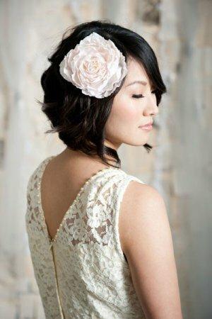 Прическа невесты с короткими волосами дополнена большим цветком.