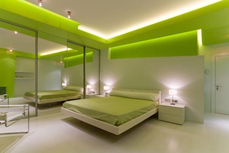 спальня в зеленых тонах со встроеным светом и большим зеркальным шкафом во всю стену