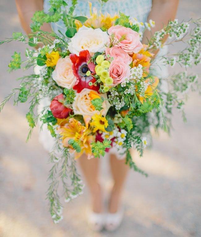 Для букета невесты и флористического оформления идеально подойдут полевые цветы и растения из вашего сада: подсолнухи, ромашки, васильки, гортензии, пионы, папоротник. Хорошо впишутся в рустикальную тематику лаванда, гипсофилы, хлопок, суккуленты, чертополох, эвкалипт и астильба. Можно добавлять колосья, шишки, ягоды, даже овощи. При выборе цветов учитывайте сезонность растений и свадьбы, это немаловажно для стиля рустик. Ножку букета можно обернуть мешковиной или кружевом.