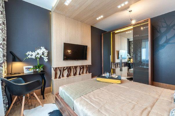Фото интерьера спальни в скандинавском стиле Деревянный каркас шкафа сочетается по цвету и фактуре с отделкой помещения,  а стекло и зеркала создают дополнительную перспективу