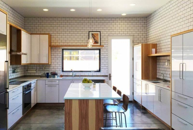 кухня из дерева с белыми глянцевыми фасадами и островом совмещающим функцию обеденного стола