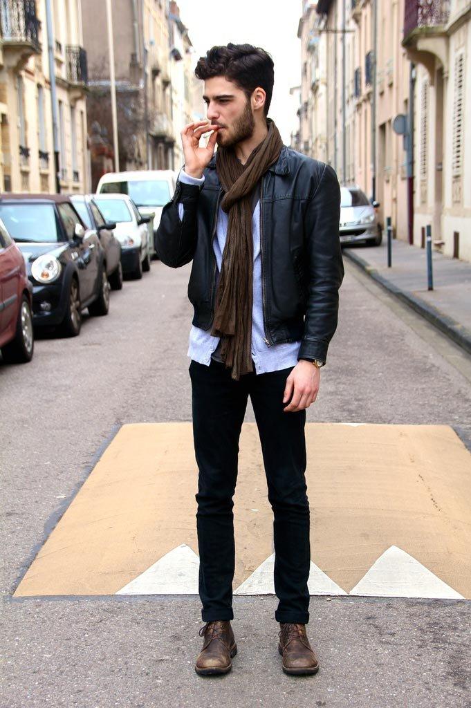Черные джинсы, голубая рубашка и черная кожаная куртка с коричневым шарфом.