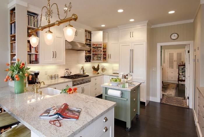 белого цвета кухня с маленьким серо-зеленого цвета островком на колесиках