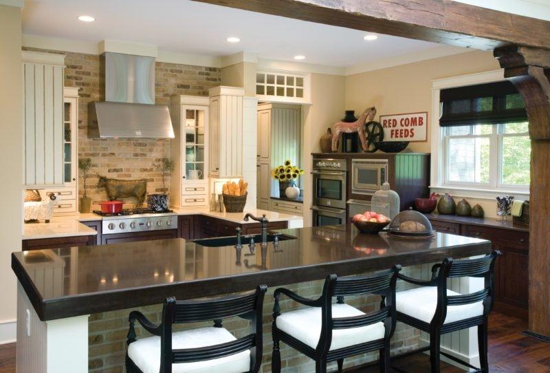 большая кухня с островом покрытым мраморной столешницей в которую врезана мойка
