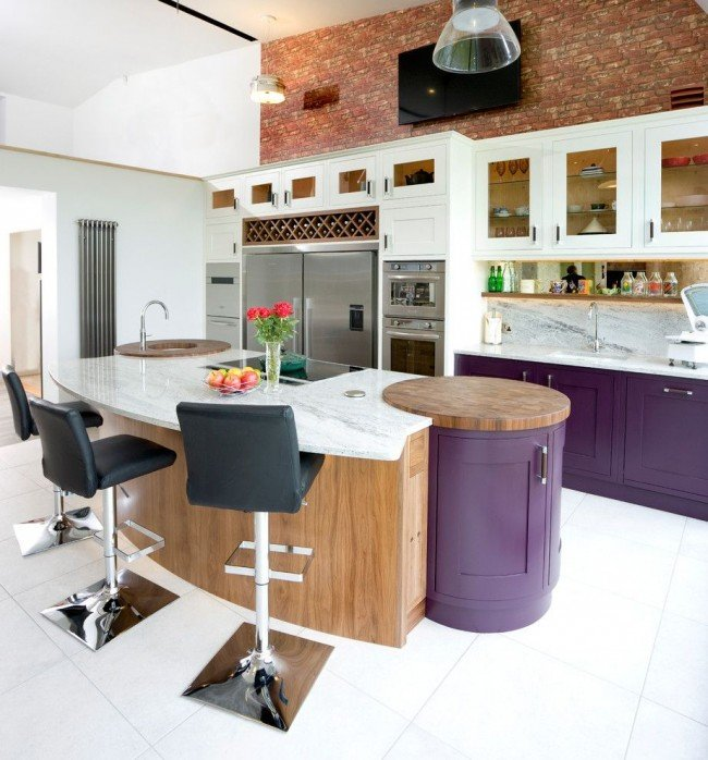 сиреневого цвета кухня с большим нестандартной формы островом