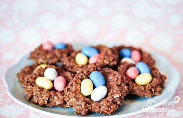 Рецепт приготовления праздничного печенья с какао, арахисовым маслом, овсяными хлопьями и конфетами в форме гнездышек с яйцами. Этот десерт станет отличным украшением стола на Пасху.