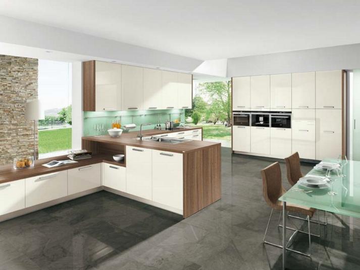 Рабочая и обеденная зона разделены, при этом в общей стилистике выполнены дизайнерские стулья и стеклянный стол в тон кухонному фартуку.