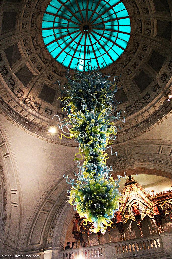 При входе в музей Виктории и Альберта поражает его оформление - прямо из-под купола свисает одиннадцатиметровая желто-голубая люстра работы американского художника-стеклодува Дэйла Чихули.
