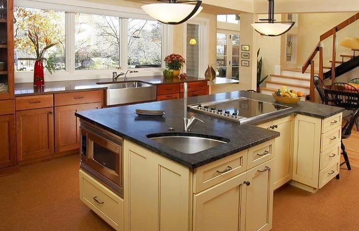 большая кухня из дерева я большим островом в форме неправильной буквы П со встроенной варочной панелью, СВЧ-печью и мойкой