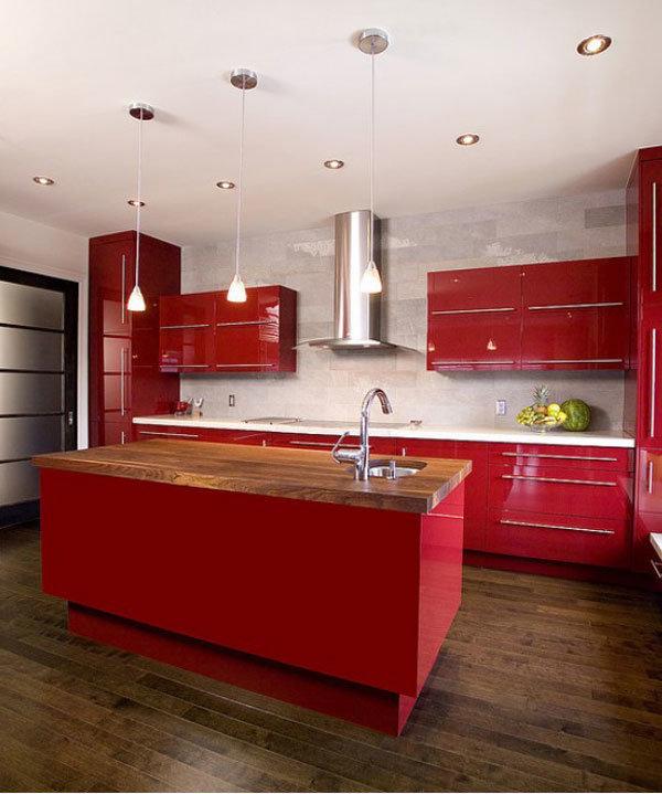 кухня выполненая в вишневом цвете с прямоугольным лаконичным островом с деревянной столешницей