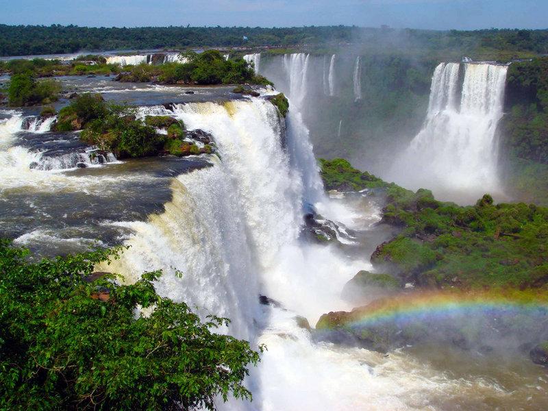 Известнейшее водное чудо природы – это Игуасу. Звонкие потоки воды, с ревом падающей, кипящей и бурлящей пеной на границе гребня у пропасти. Загадочное преломление и мерцание света, поразительные радуги, которые танцуют в алмазном тумане брызг. Гармония двух сотен струй, вечность мироздания и первобытная невозмутимая мощь. Это все про водопад Игуасу. Он уникальный по всем параметрам. Это трудно представляется, кажется невозможным, а эмоции, вызывающие данное зрелище, мечтают получить все жители планеты Земля.  Игуасу  слагается из цепочки в 275 водопадов, которые образуют в виде подковы каскад белоснежных потоков. Он шире, чем водопад Виктория, потому что его длина свыше трех километров. Он выше, чем Ниагарский водопад, потому что его струи обрушиваются с высоты восьмидесяти метров.