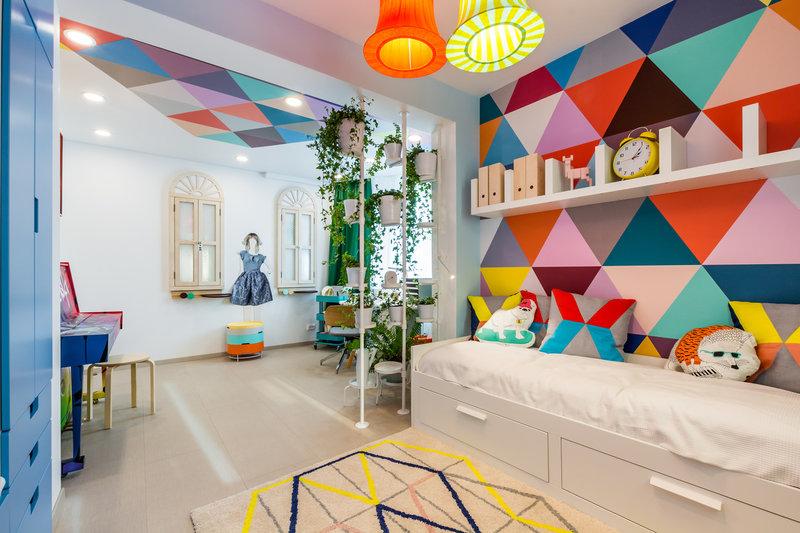 Яркий орнамент на стене поддерживают диванные подушки и общий декор комнаты