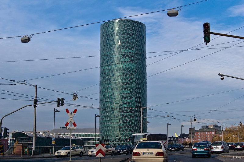 """Франкфуртский даунтаун - Westhafen Tower - башня высотой 109 метров построенная в 2004 году. Ее название означает """"Западная башня порта"""". Снаружи задние имеет форму цилиндра, но этажи квадратной формы. Внешнее цилиндрическое покрытие состоит из треугольных 3556 стекол. Часть стекол может автоматически открываться для улучшения вентиляции."""